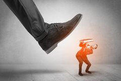 Large foot stepping down small man. Large formal shoe stepping down young small entrant mann royalty free stock photo