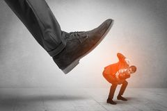 Large foot stepping down small man. Large formal shoe stepping down young small entrant mann stock photography