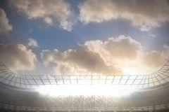Large football stadium with spotlights under blue sky with clouds. Digitally generated large football stadium with spotlights under blue sky with clouds Royalty Free Stock Photography