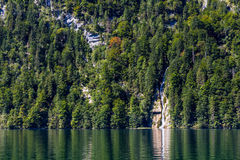 Large forest waterfall into lake with its reflections at lake of Konigsee in Bavaria, Germany Royalty Free Stock Photo
