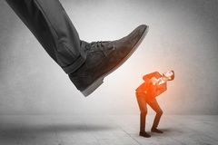 Large foot stepping down small man. Large formal shoe stepping down young small entrant man royalty free stock photography