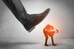 Large foot stepping down small man. Large formal shoe stepping down young small entrant man stock image