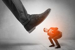 Large foot stepping down small man. Large formal shoe stepping down young small entrant mann royalty free stock images