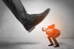 Large foot stepping down small man. Large formal shoe stepping down young small entrant mann stock images