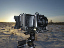 Large Format Camera in the Field. A large format camera (4x5) in a snowy field shortly after sunrise Stock Image