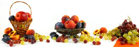 Large-format panorama with fruit on a light background. Large-format panorama of still life with apples, peaches, plums and grapes on a light background royalty free stock images