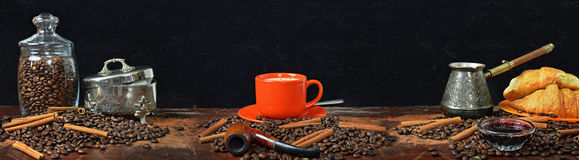Large-format panorama of a still life on a coffee subject. Still life panorama with coffee grains, with a coffee mug, with croissants and jam Stock Photos
