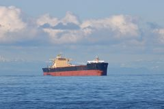 Large Freighter in Calm Sea. An  view of a large freighter ship surrounded by calm ocean waters and cumulus clouds Royalty Free Stock Photos