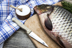 A large fresh carp live fish lying on a wooden board with a knife and slices of lemon and with salt dill. Royalty Free Stock Images