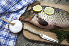 A large fresh carp live fish lying on a wooden board with a knife and slices of lemon and with salt dill. Stock Image