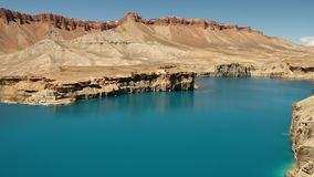 Large freshwater turquoise blue lake basin. Travertine cliffs surrounded by mountains. Band-e Amir Lakes. Band-e Amir National Park, Bamyan Province stock footage