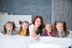 Large friendly family, many children: mom and four pretty cheerful girls triple twins sisters lying on a bed against a gray brick stock photo