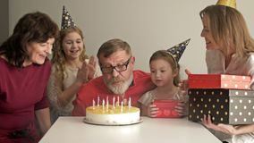 Large friendly multi-generation family standing together in home and watching grandfather blowing candles on birthday
