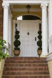 Large front door with white exterior with brick steps. And white pillars, potted plants, shrubs in a residential neighborhood Stock Images