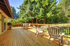 Large frsehly painted new wooden deck with nice summer green bac. Large freshly painted new wooden deck with nice summer green backyard and outdoor furniture Royalty Free Stock Photos
