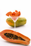 The large-fruited Papaya. A papaya fruit in longitudinal section, its fruit pulp assorted in a cocktail glass and a whole fruit Stock Photos