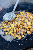 A large frying pan with fried new potatoes at the fair food. Young potatoes fried in boiling oil to a large frying pan over an open fire royalty free stock image