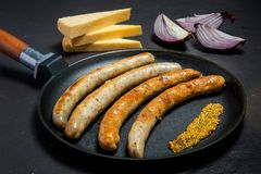 Large frying pan with fried thin sausages and granular mustard. Large frying pan with fried thin meat sausages and granular mustard served with few pieces of royalty free stock photography