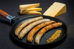 Large frying pan with fried thin sausages and granular mustard. Large frying pan with fried thin meat sausages and granular mustard served with sliced hard stock image