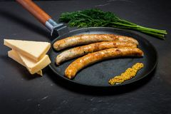 Large frying pan with fried thin sausages, mustard, dill, and cheese. Large frying pan with fried thin sausages and granular mustard served with green dill and royalty free stock photo