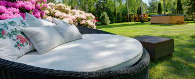 Large garden sofa with cushions. Panoramic view of large garden sofa with decorative cushions Stock Photo