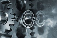 Large gear-mechanism and titanium. Large industrial gear-mechanism and titanium, mirrred in background in a blue-metallic tone Royalty Free Stock Images