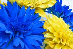 Large Giant Paper Flowers. Big blue and yellow dahlias made from paper. Pastel paper background pattern lovely style. Flower made. From corrugated paper and EVA stock photos