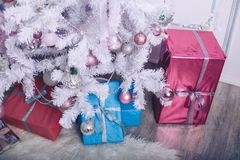 Large gift boxes under the New Year tree. Large gift boxes under the New Year`s white Christmas tree Stock Image