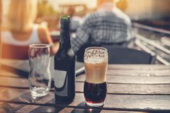 A large glass and a bottle of dark beer on the background of the pub on a wooden table. Tinted glass. Copy space. The Royalty Free Stock Photography