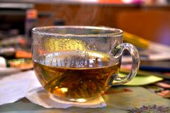 A large, glass cup with very hot Chinese, floral, bound tea royalty free stock images