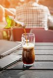 A large glass of dark beer on a pub background on a wooden table. Tinted Windows. The vertical frame Stock Photo