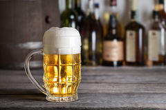 Large glass of light beer with foam on bar counter. Against background of drums Royalty Free Stock Photography