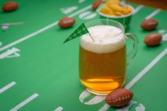 Large glass mug of cold beer on table with superbowl party decor. Mug of beer on snack table decorated for superbowl party royalty free stock photo