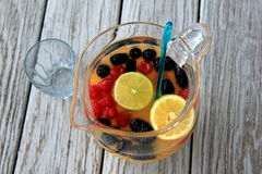 Large glass pitcher and ladle with juice and seasonal fruit Royalty Free Stock Photography