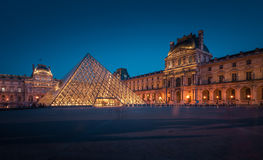 The large glass pyramid and the main courtyard of the Louvre Museum at dusk. Stock Photos
