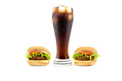 Large glass of soda beside two burgers on the sides isolated on white Stock Photos