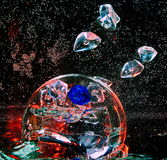 Large glass transparent ball inside the water with air bubbles a. Nd colorful pieces of artificial ice Stock Images