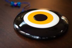 Large glass Turkish evil eye on wooden table stock photo