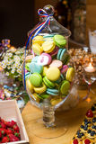 Large glass vase with macaroon is on the dessert table. Macaroon in a glass vase on a table in сandy bar royalty free stock image