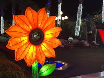Large glowing lightbulbs from light bulbs yellow paper decorative flower of a sunflower with petals festive decoration in a night. Festive city, in a park on a royalty free stock photo