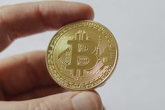 A Large Gold Bitcoin Token in hand. A gold Bitcoin token in hands Royalty Free Stock Photo