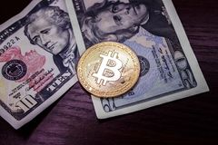Large gold coin bitcoin and dollars. Gold coin bitcoin next to the bills of American dollars Stock Photos