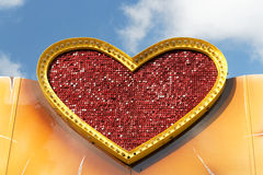 Large gold heart shape. Large heart shape with gold border around a  red textured  surface viewed against a blue sky background Royalty Free Stock Image