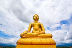 Large golden buddha statue on cloudy blue sky background Royalty Free Stock Photography