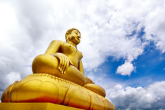 Large golden Buddha statue on cloudy blue sky background Royalty Free Stock Photo