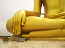 Large golden buddha statue with his big hand and fingers at WAT MUANG Muang Temple Ang Thong Province, THAILAND royalty free stock photo