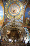 The large golden chandelier with the colorful icons on the background in church Royalty Free Stock Photo