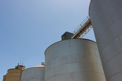 Large Grain Silos. Large steel grain silos with cloudless blue skies Stock Photo