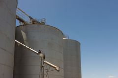Large Grain Silos. Large steel grain silos with cloudless blue skies Royalty Free Stock Image