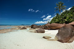 Large granite boulders on the white sandy beach Royalty Free Stock Images